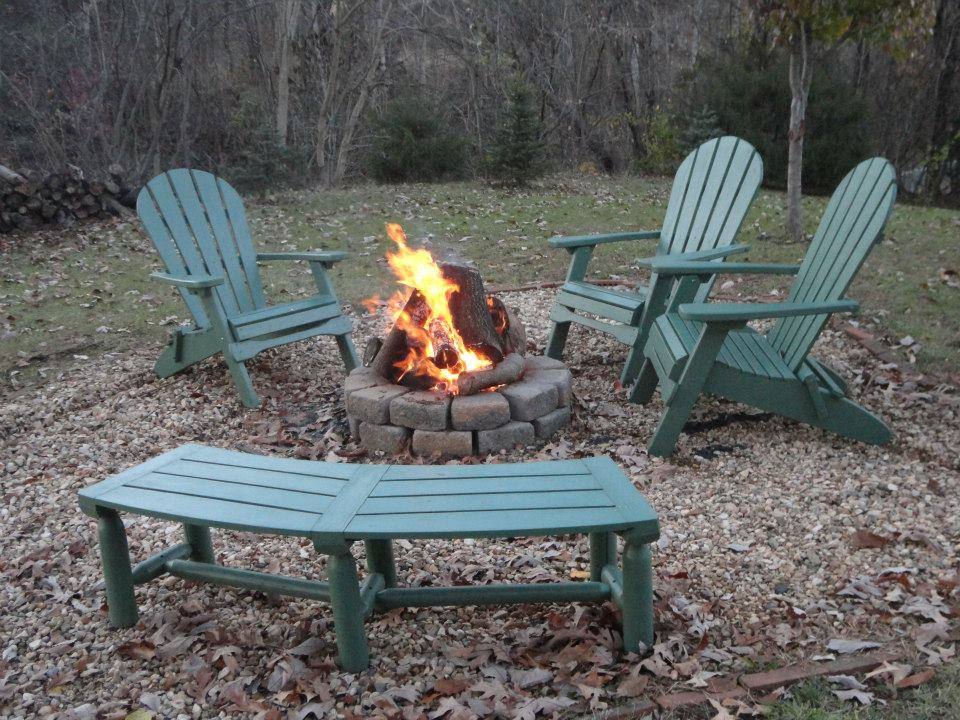 fire in firepit with chairs around them
