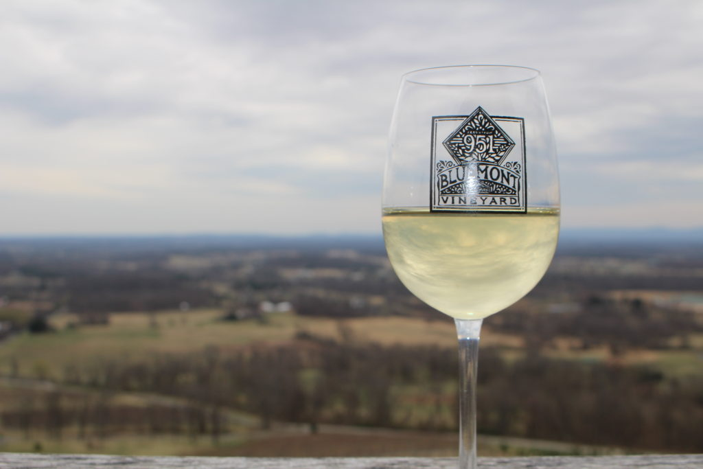 A glass of wine from Bluemont Vineyard with the scenic mountain view beyond
